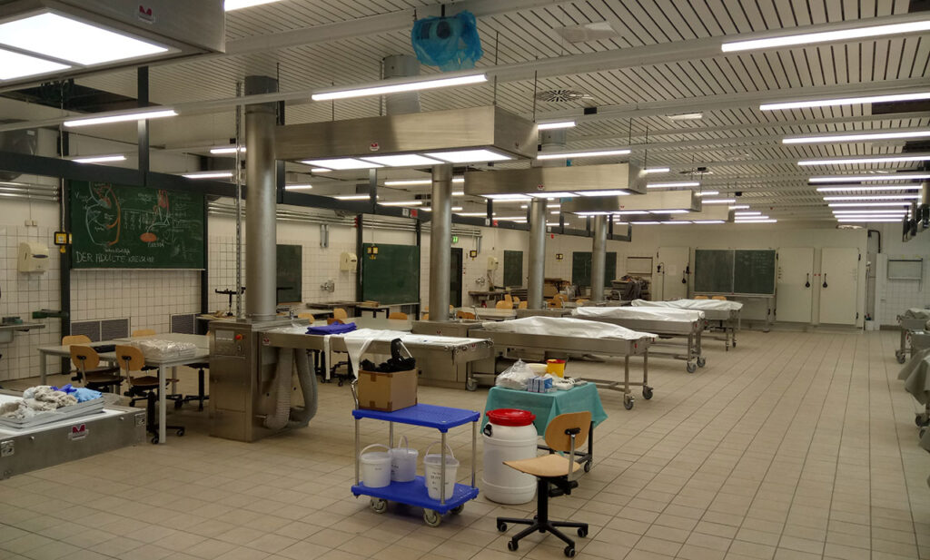 Dissecting room fully equipped with MEDIS anatomy technology system incl. fresh air supply unit with LED-illumination, sink and mobile student dissecting table with donor-bodies. Extraction of formaldehyde fumes through ceiling. Loading / unloading of bodies automatically.